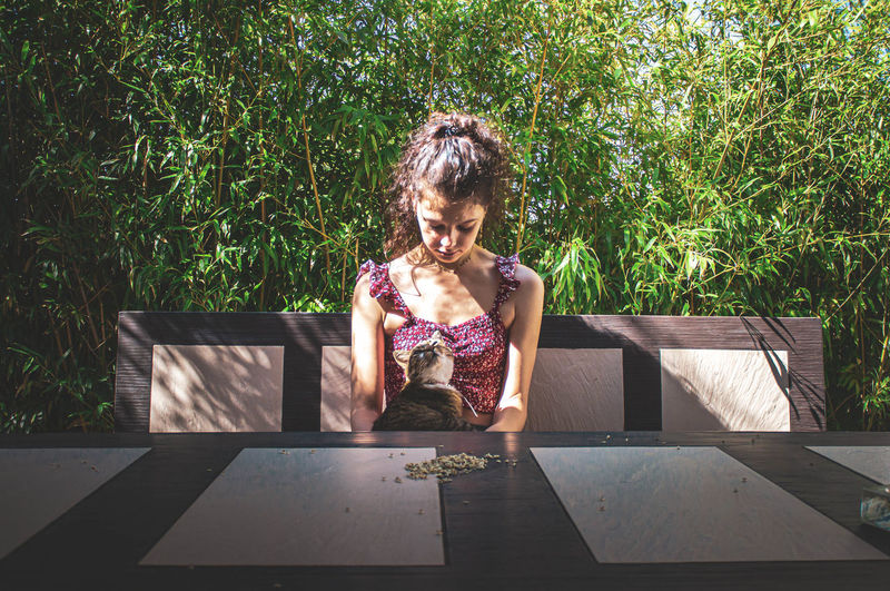 Young woman sitting on table against plants