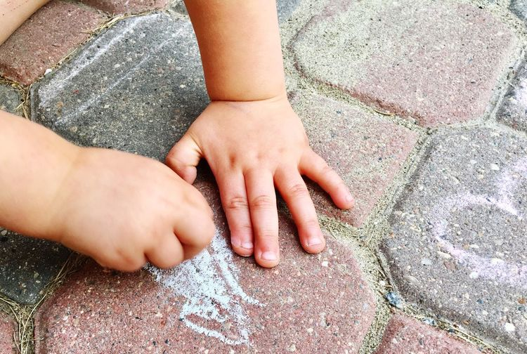 Cropped hands of baby drawing on footpath