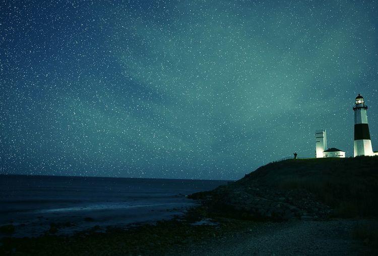 Illuminated Montauk Point Light On Shore Against Star Field At Night