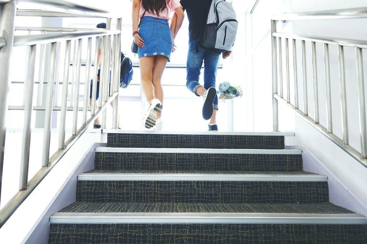Low angle view of couple climbing stairs at airport