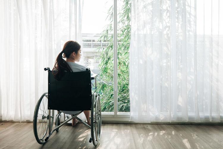 Woman sitting on window in a room