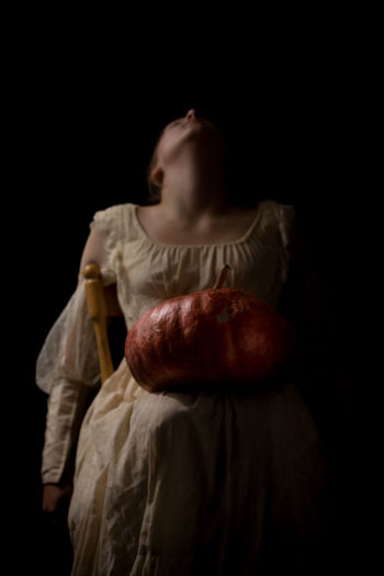 Girl with pumpkin against black background