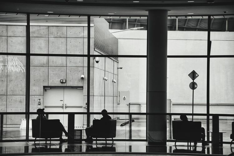 Rear view of people sitting in airport building