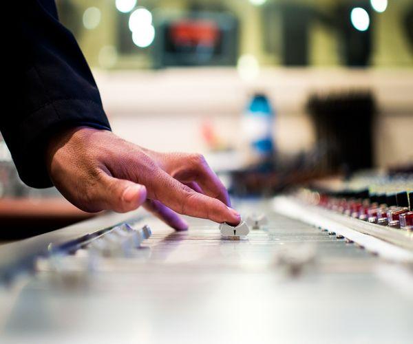 Midsection of dj adjusting volume