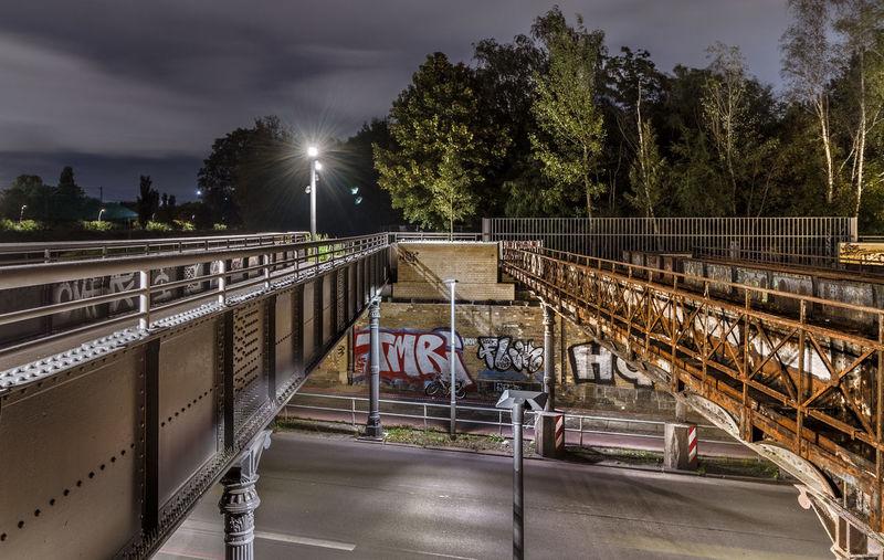 Bridge over illuminated street against sky at night