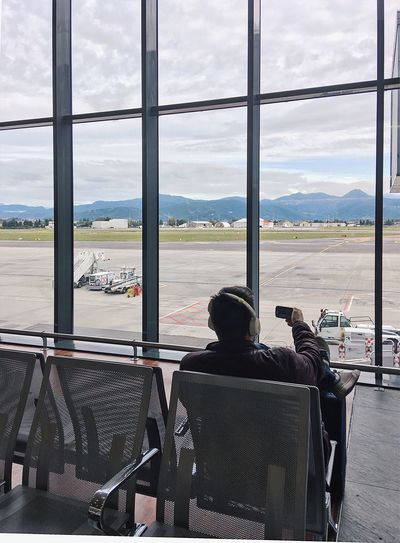 Man doing selfie in the airport Airport Airplane Window Air Vehicle Rear View Airport Runway Indoors  Cloud - Sky Transportation Travel One Person Real People Flying Self Portrait Only Women Music Listening To Music Italy Bergamo