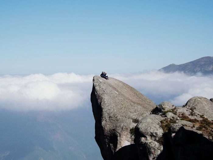 Couple Sitting On Top Of Cliff Against Clouds Covering Mountains