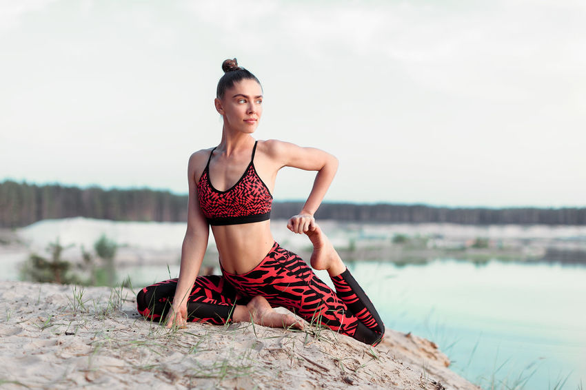 A beautiful girl in sports clothes is engaged in yoga in nature near the lake and pine forest Meditation Yoga Yoga Pose Caucasian Ethnicity Day Fitbody Fitness Training Fitnessmodel Fitnessmotivation Girl Harmony With Nature Lake View Leisure Activity Lifestyles Motivation Bodybuilding Inspiration Fitness Nature One Person Real People Sky Sport Woman Sports Clothing Stretching Successful Workout Yoga Practice