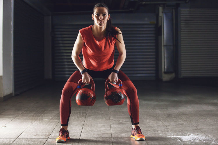 Full Length Portrait Of Woman Lifting Kettlebells At Gym