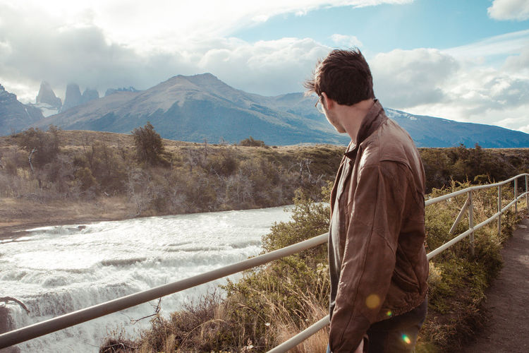 Man standing by railing and river against sky