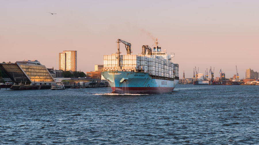 Hamburg skyline with massive container ship in the foreground Water Nautical Vessel Transportation Architecture Sky Ship Waterfront Mode Of Transportation Building Exterior Built Structure Clear Sky City Motion Outdoors Business Skyline Cityscape River Container Ship Harbor Harbour Travel