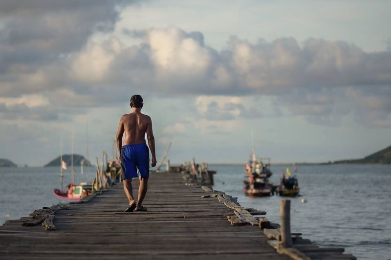 Rear view of shirtless man walking on pier over sea against sky at sunset