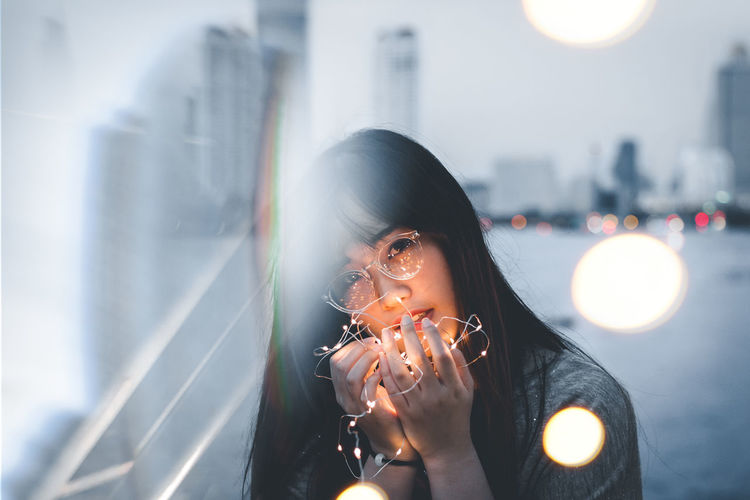 Portrait of woman holding camera in city