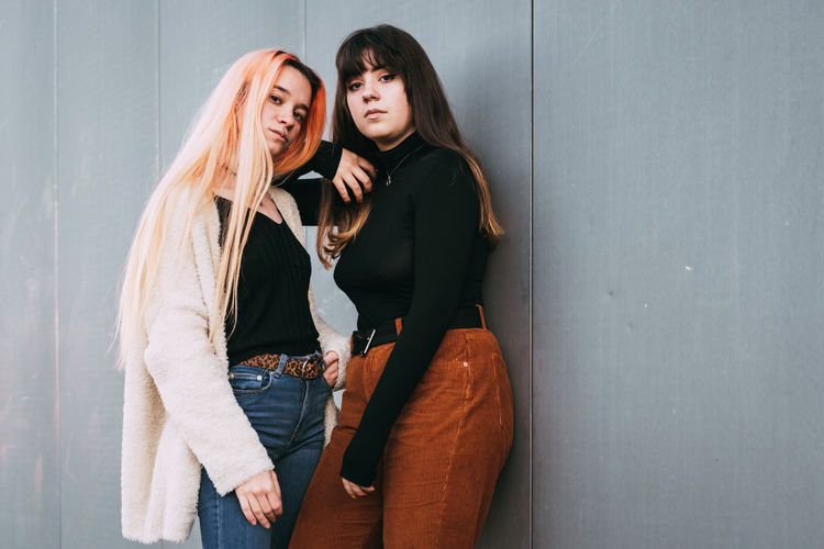 Portrait of friends standing against wall