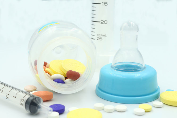 Close-up of medicines spilling from baby bottle with syringes on blue background