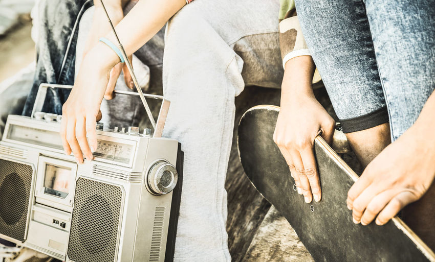 Midsection of friends holding skateboard and radio while sitting outdoors