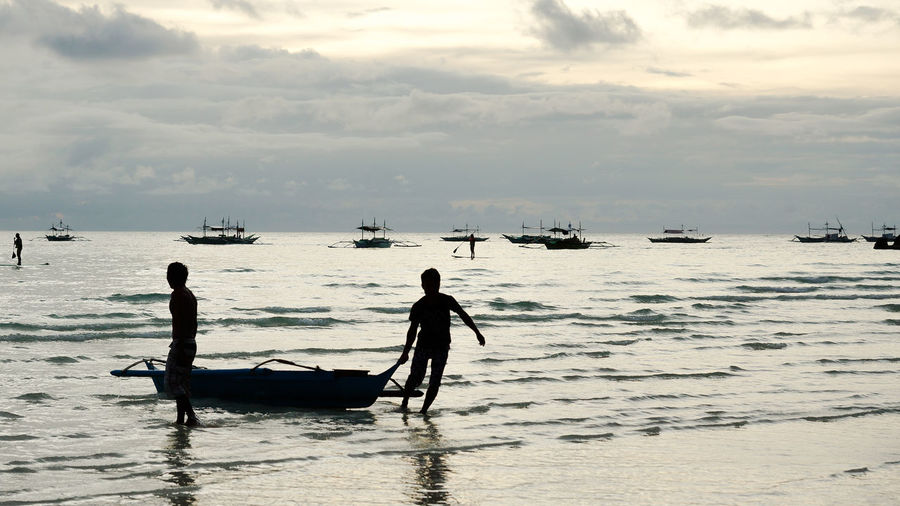 Young men dragging small fishing boat to shore during island sunset Beach Beach Life Beach Sunset Boracay Community Filipino Culture Fishermen Fishing Boat Fishing Village Island Life Island Sunset Island View  Islanders Islands It's More Fun In The Philippines Men Philippines Photos Silhouette Silhouettes Simple Life Sunset The Philippines Village Scene Village View White Beach