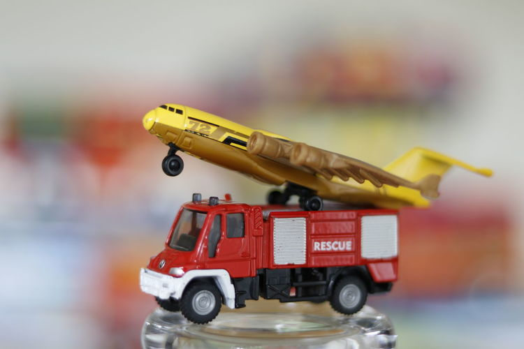 Close-up of airplane model on fire engine toy