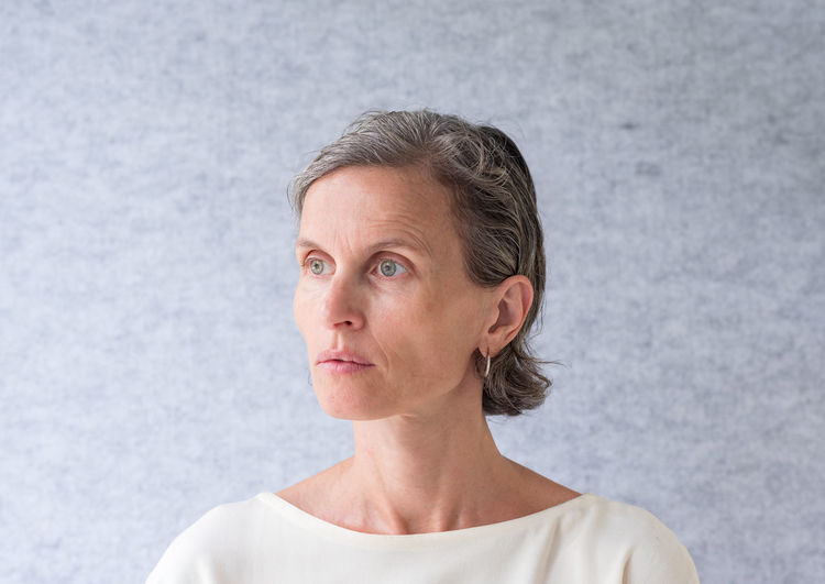 Portrait of middle aged woman Headshot Portrait One Person Front View Adult Mature Adult Women Gray Contemplation Indoors  Copy Space Looking Studio Shot Serious Gray Background Casual Clothing Introspection Looking Away Hairstyle Beautiful Woman