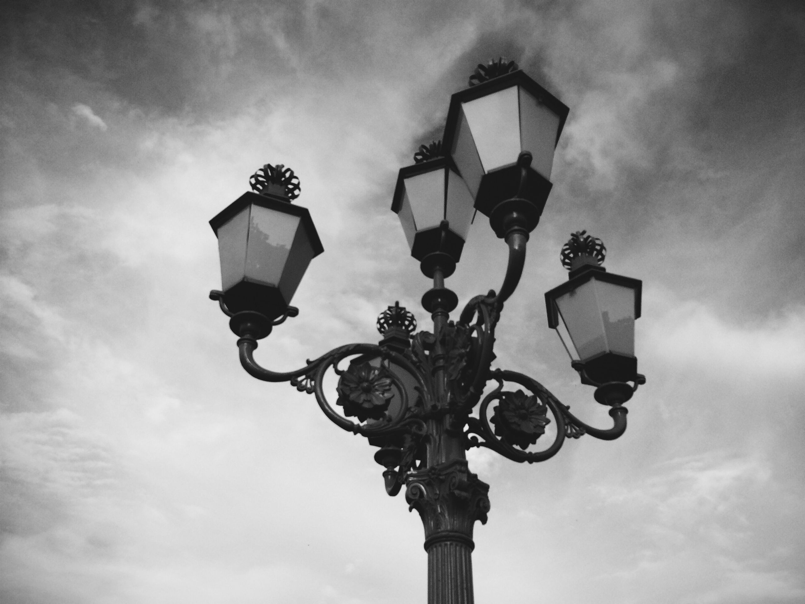low angle view, sky, lighting equipment, street light, cloud - sky, cloudy, cloud, built structure, no people, hanging, day, electric lamp, outdoors, electric light, pole, lantern, lamp post, architecture, metal, electricity