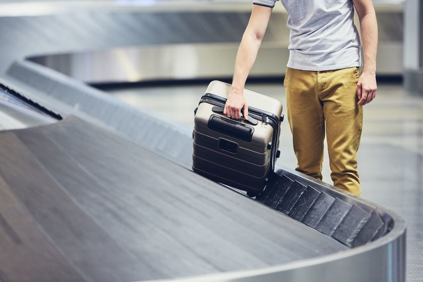 Man (traveler) picking up suitcase from baggage claim in airport terminal. Conveyor Belt Lost Man Passenger Tourist Transportation Travel Airport Airport Terminal Arrival Baggage Baggage Claim Casual Clothing Flying Holding Indoors  Journey Low Section Luggage One Person People Real People Suitcase Tourism Transportation