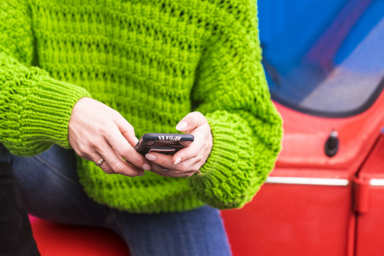 Close up of modern concept of technology internet connected devices and addicted people - coloured image of millennial girl using cellular phone messaging or sharing on the web - Midsection One Person Holding Adult Wireless Technology Casual Clothing Technology Communication Women Clothing Sweater Focus On Foreground Front View Human Hand Connection Close-up Leisure Activity Lifestyles Portable Information Device Hand Warm Clothing Jeans Addiction Fashion Using Mobile Phone Telephone Line Caucasian Colorful Red Car