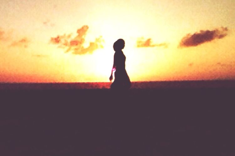 Silhouette of woman at sunset