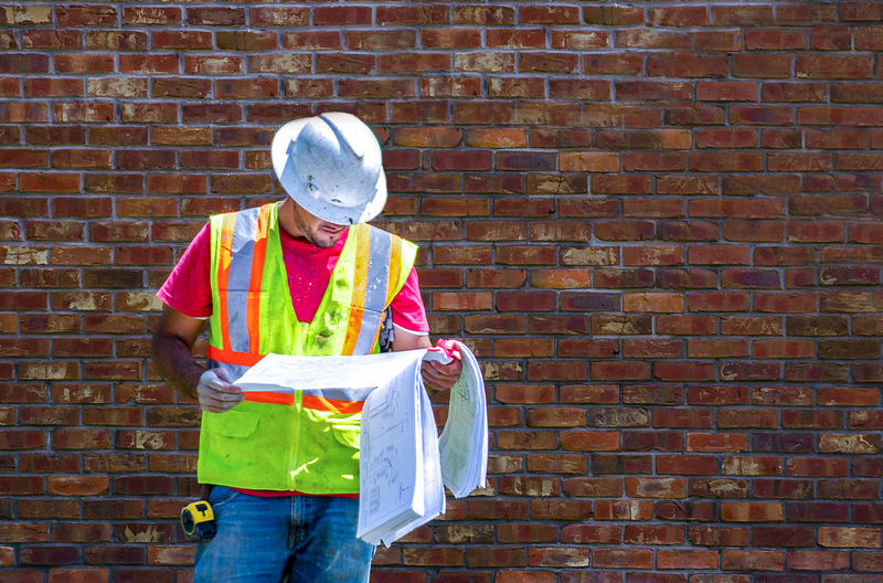 Construction Worker Holding Blueprint While Standing Against Brick Wall