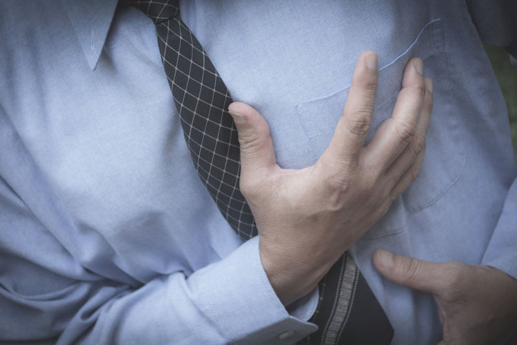Midsection of businessman suffering from chest pain