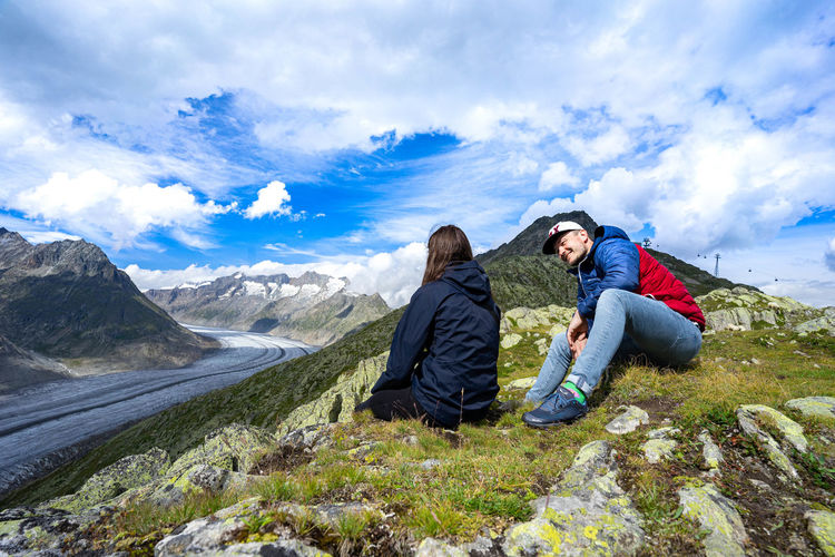 Friends sitting on mountain against sky