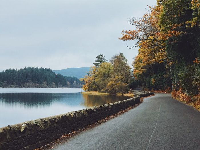 Road by lake against sky during autumn