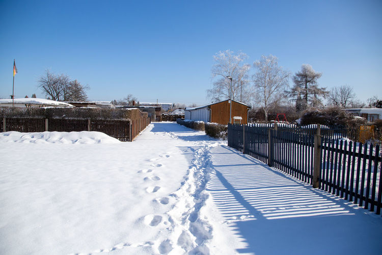 Snow covered fence against sky