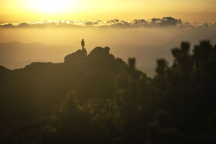 Silhouette person on rock against sky during sunset