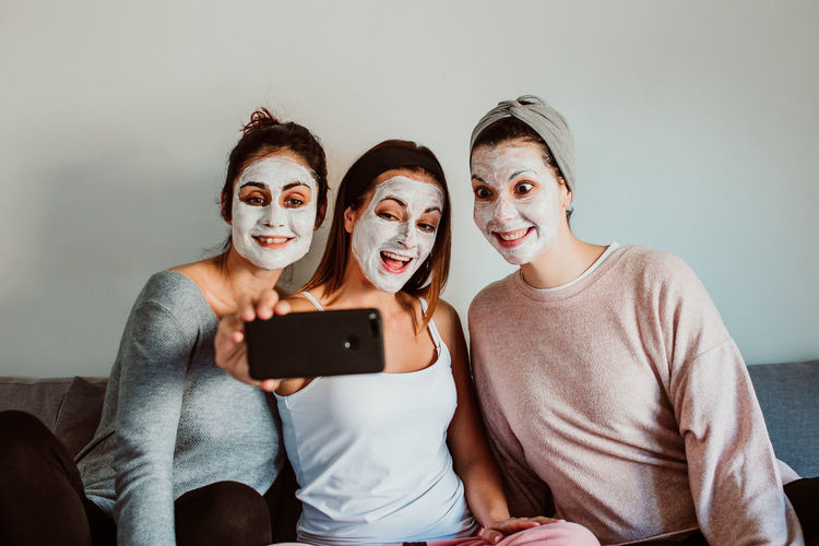 Female friends with facial masks taking selfie with against wall at home