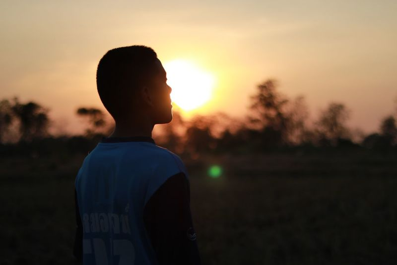 Thoughtful teenage boy standing against sky during sunset