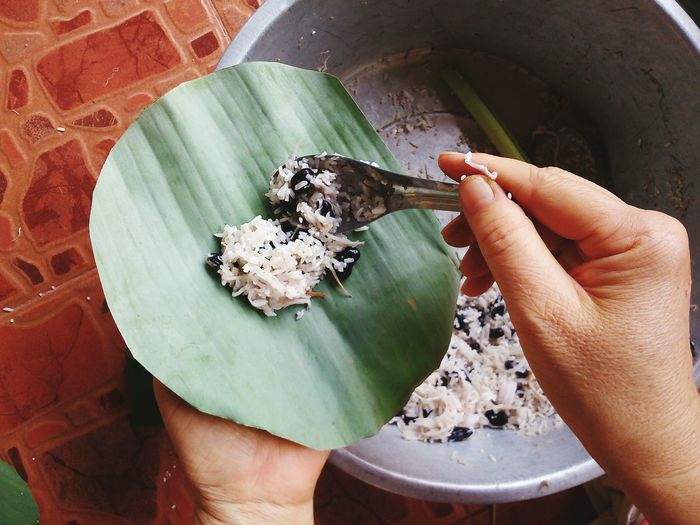 Cropped hand filling banana leaf with rice and bean