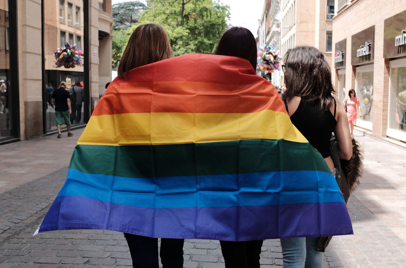 Rear view of women with rainbow flag standing on street