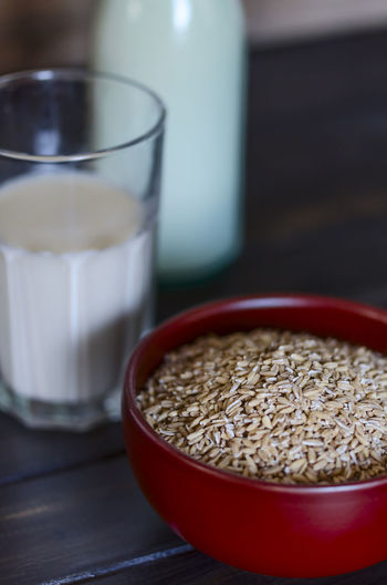 High Angle View Of Oats In Bowl With Glass Of Milk On Table At Home