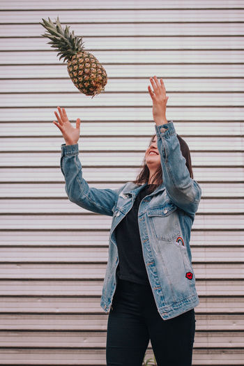 Woman Playing With Pineapple While Standing Against Wall