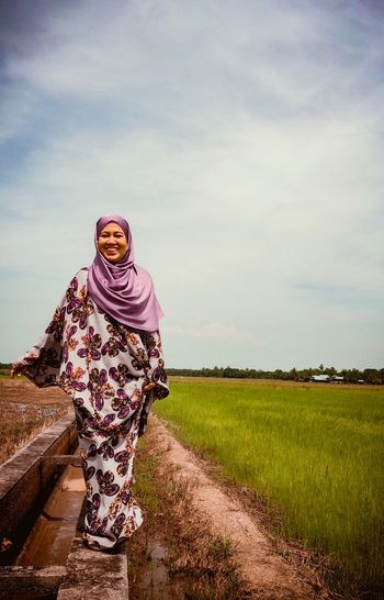 Portrait of smiling woman wearing hijab standing on land against sky