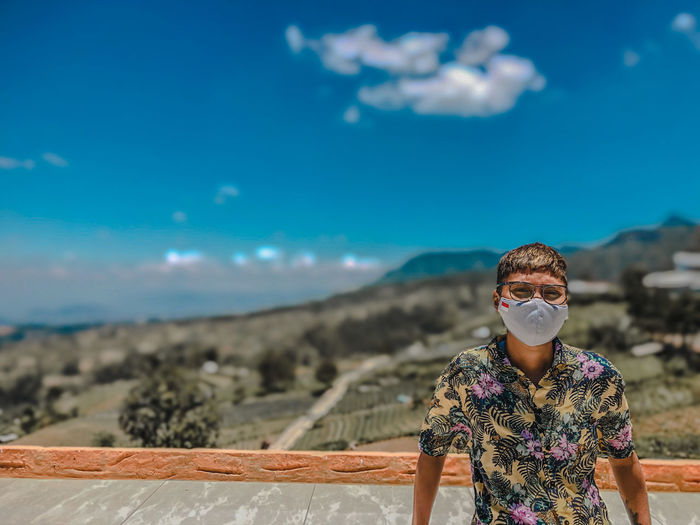 Portrait of young man wearing mask standing against blue sky