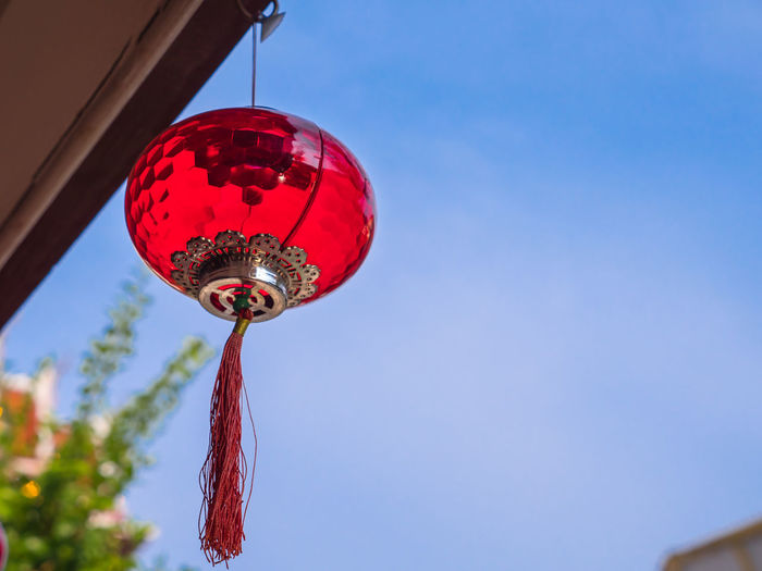 Low angle view of lantern hanging against blue sky