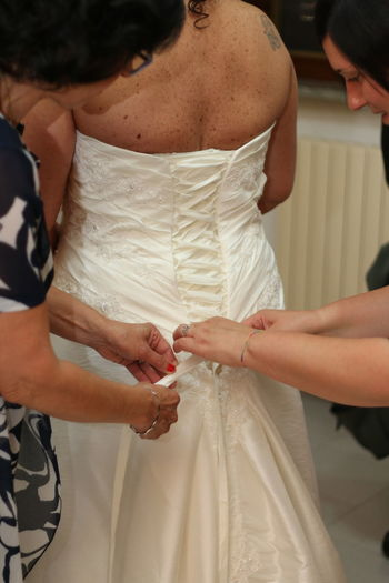 Midsection of women helping bride to get dressed