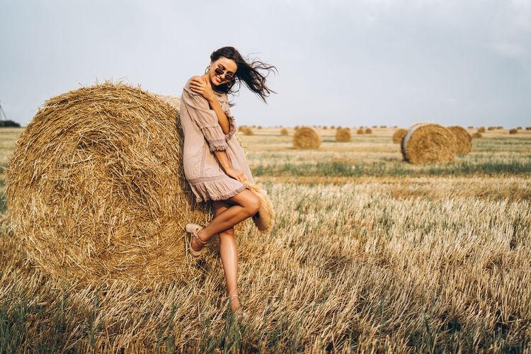 Full length of woman wearing hay bales on field against sky