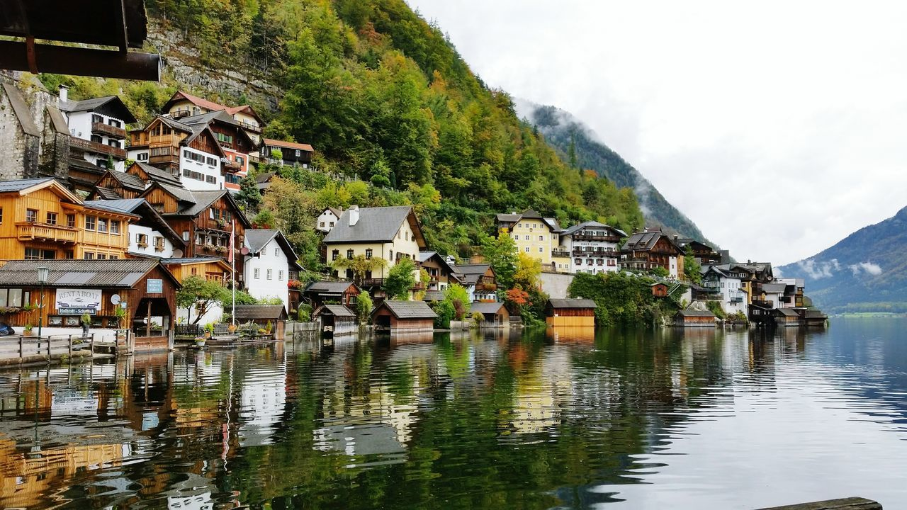 mountain, building exterior, water, architecture, built structure, day, outdoors, mountain range, house, waterfront, sky, nature, beauty in nature, lake, scenics, no people, tranquility, tree