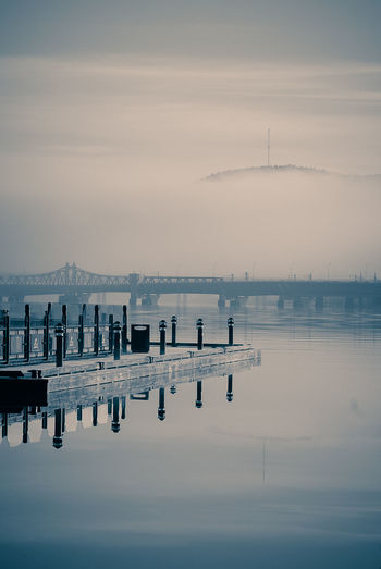 Pier by river against sky during foggy weather