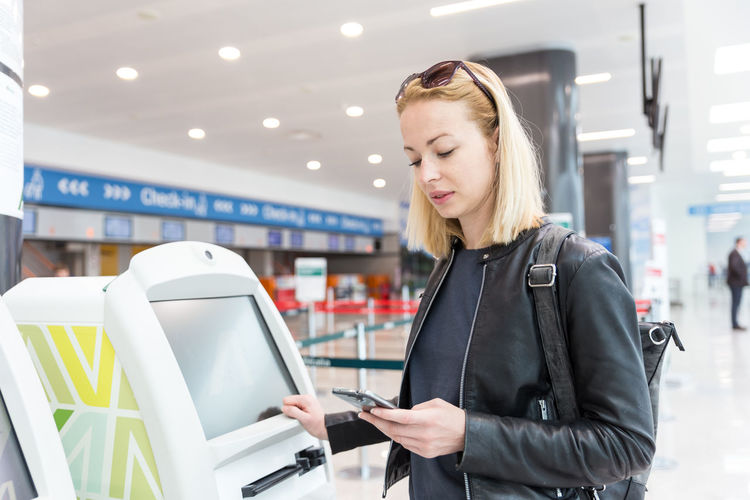 Beautiful woman standing by atm machine at airport