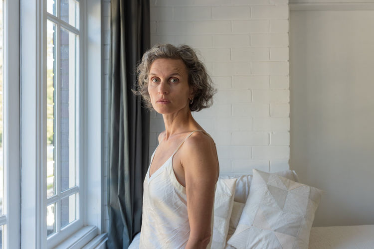 Woman at window One Person Portrait Indoors  Lifestyles Window Looking Contemplation Women Standing Day Looking At Camera Adult Hair Beauty Beautiful Woman Real People Leisure Activity Hairstyle Mature Women