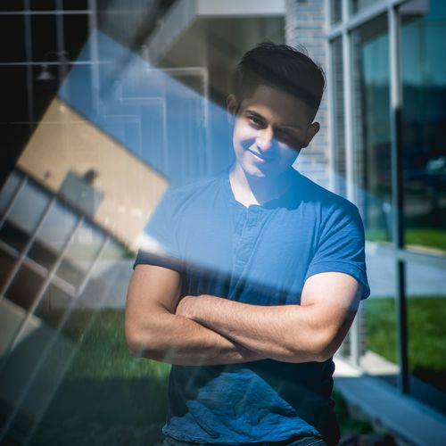 Portrait of confident young man seen through glass