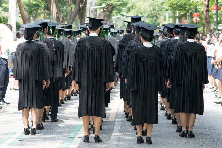 Rear view of students in graduation gown standing at university campus